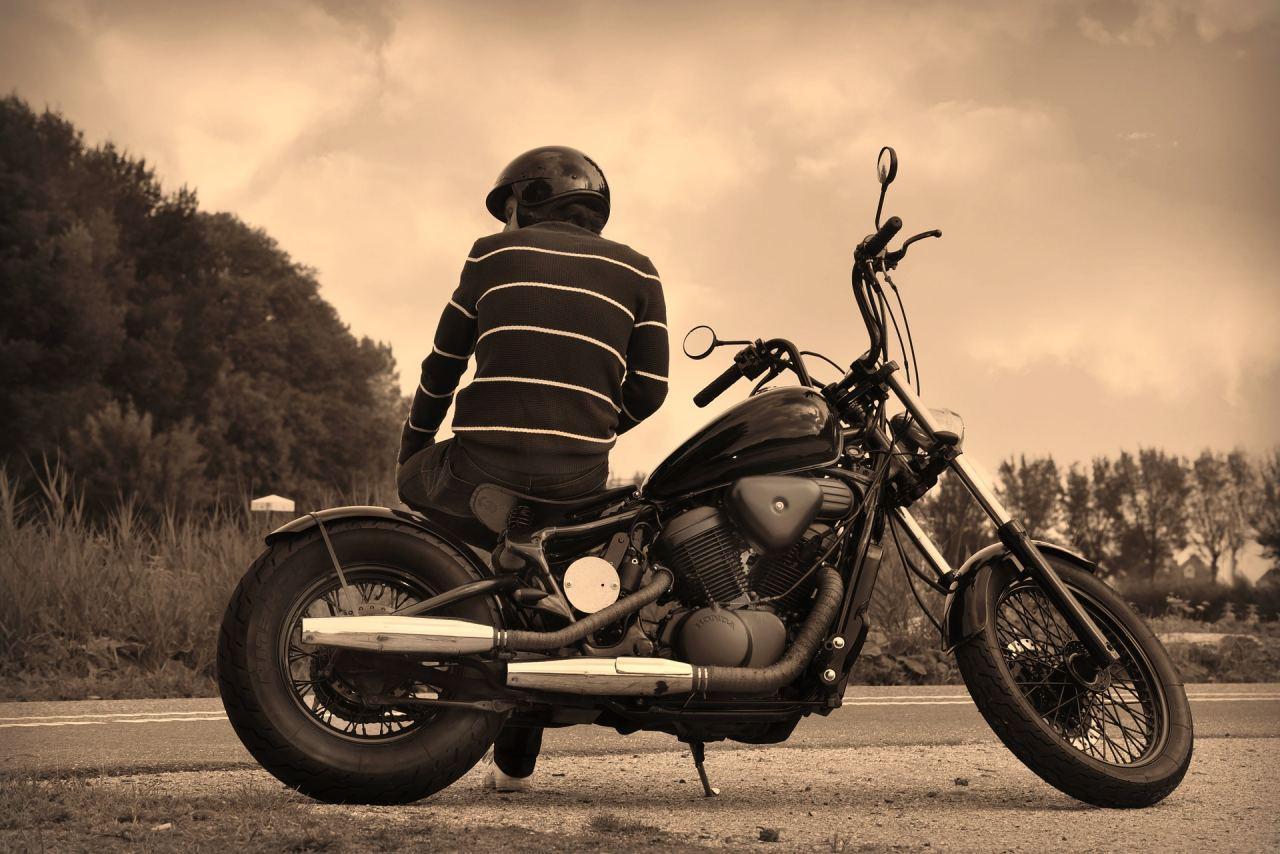 Mann lehnt an seinem Motorrad
