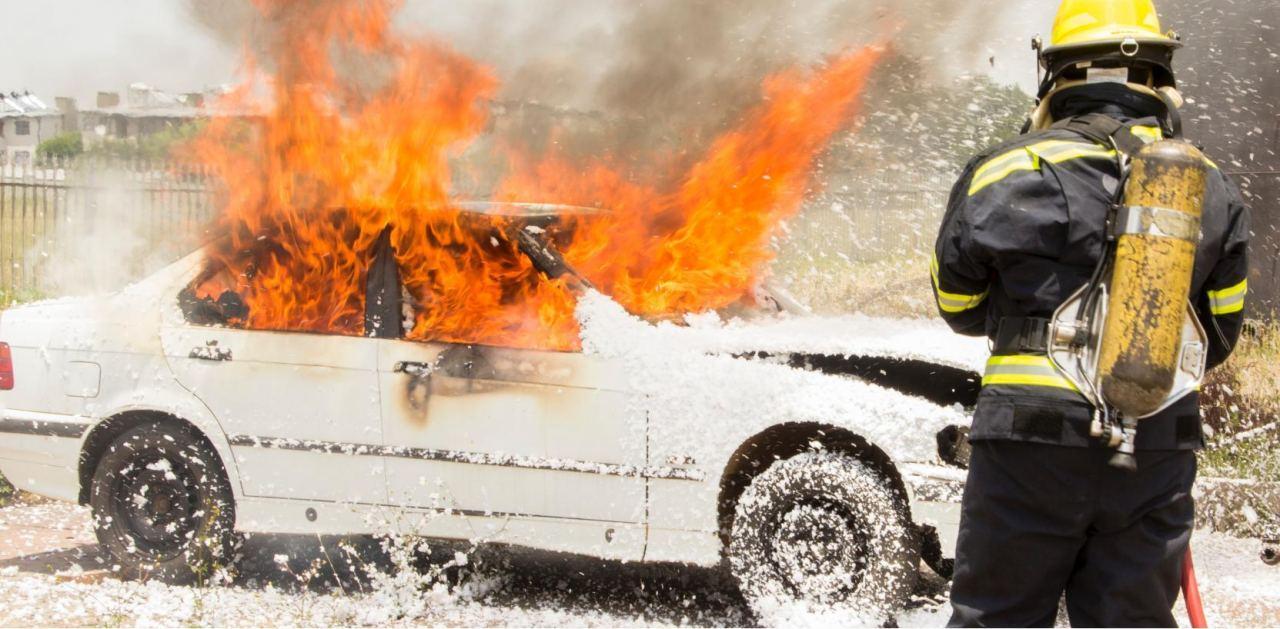 Brennendes Auto wird von Feuerwehr gelöscht